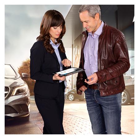 Daimler Angestellte die einem Kunden auf einem Tablet etwas veranschaulicht