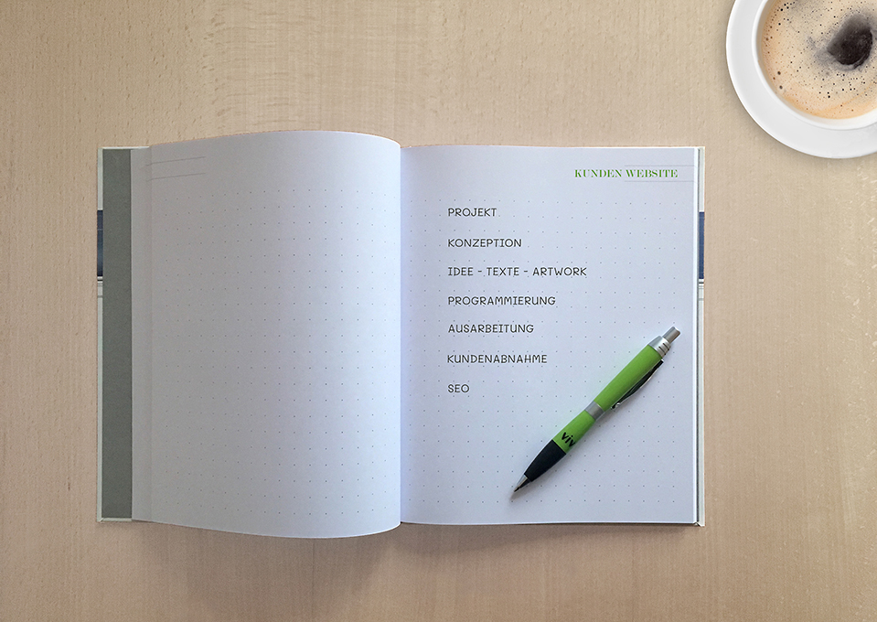 Aufgeschlagenes Notizbuch auf einem Tisch mit Werbekeywords wie Projekt, Konzeption oder Programmierung