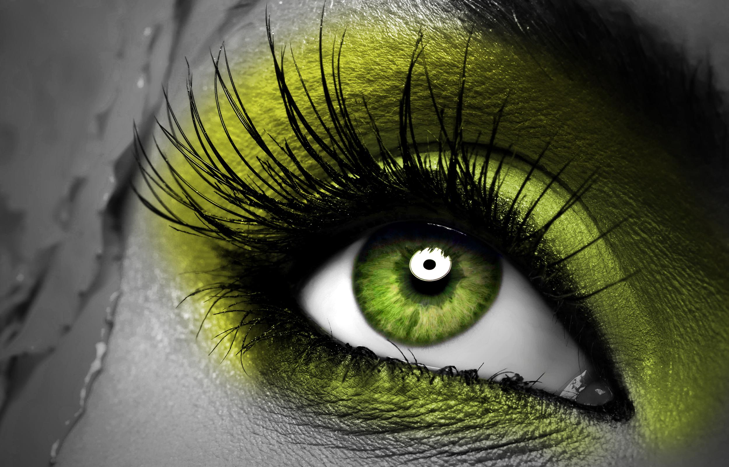 Scharfes Auge mit grüner Pupille und grünem Lidschatten mit langen Wimpern